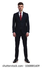 handsome businessman posing while standing on white background, wearing a navy suit and a red tie, full body picture