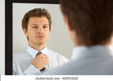 Handsome businessman preparing to official event, straighten tie. New job interview, self motivation for confidence, trying fashionable necktie knot, tailor service or dating concept