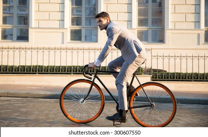 Handsome businessman riding bicycle to work on urban street in morning