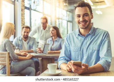 Handsome businessman in shirt is using a smart phone, looking at camera and smiling, in the background business people are co-working