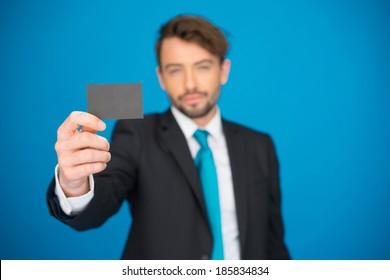 handsome businessman showing blank business card on blue