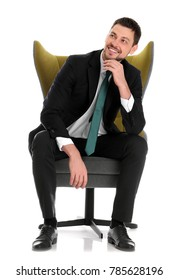 Handsome businessman sitting in comfortable armchair on white background