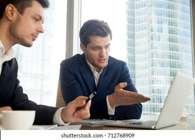 Handsome businessman sitting at desk with partner and pointing on laptop screen when explaining project advantages. Business leaders discussing details of companies collaboration. CEO presenting offer