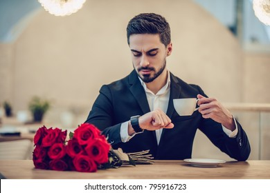 Handsome businessman is sitting in modern restaurant with bouquet of red roses and checking the time while waiting for his beloved.