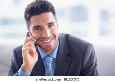 Handsome businessman sitting on sofa making a call smiling at camera in the office