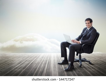 Handsome businessman sitting on a swivel chair and using his laptop on decking with heavenly backdrop