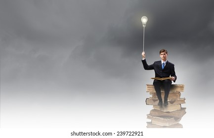 Handsome businessman sitting on top and reading book