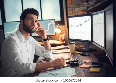 Handsome businessman sitting and using computer thinking of trading graph beside the windows over the stock exchange trading graph screen background. Indoor, studio shot. Trade concept