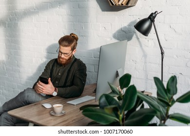 handsome businessman sitting and using smartphone in office