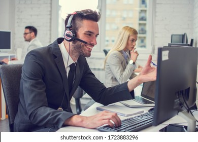 Handsome businessman sitting working on computer in office.