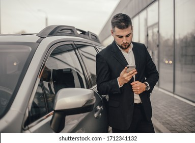 Handsome businessman with smartphone near vehicle on office parking