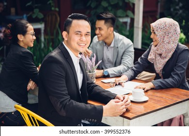handsome businessman smiling at the camera during a business meeting