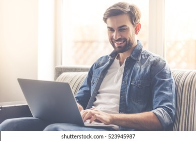 Handsome businessman is smiling while working with a laptop at home