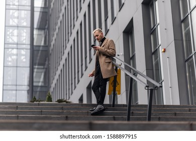 Handsome businessman standing in a beige coat with crossed legs and looking at the phone.