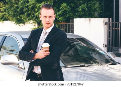 Handsome businessman  standing with coffee cup near the car