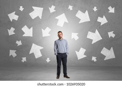 Handsome businessman standing in front of a wall with chalk drawn arrows