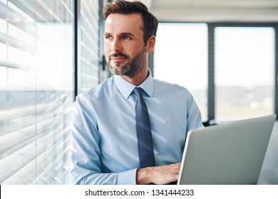Handsome businessman standing with laptop, looking throught the window in modern office