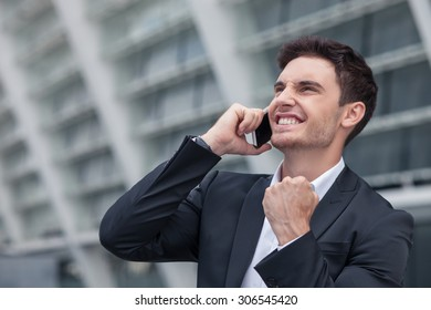 Handsome businessman is standing and talking on the phone with his client. The deal was done successfully. The worker is smiling and raising his fist up happily