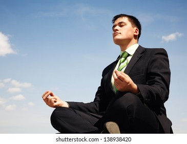 Handsome businessman in suit doing yoga