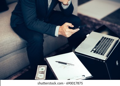 Handsome businessman in suit and eyeglasses speaking on the phone in office,Side view shot of a man's hands using smart phone in rear view of business man busy using cell phone at office.