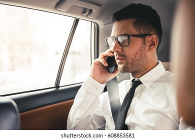 Handsome businessman in suit and eyeglasses is talking on the mobile phone while sitting on back seat in the car