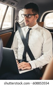 Handsome businessman in suit and eyeglasses is using a laptop while driving on back seat in the car
