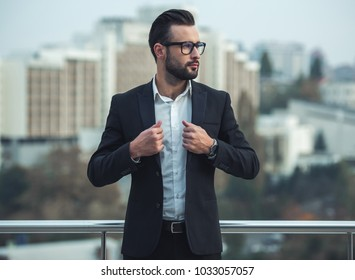 Handsome businessman in suit and glasses is looking away while standing on the balcony