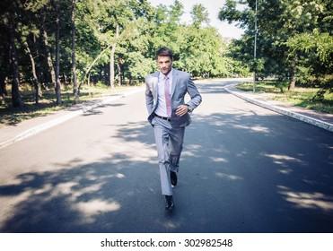 Handsome businessman in suit running in park