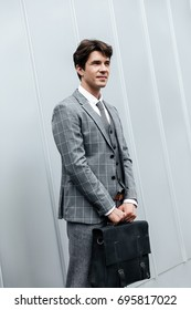 Handsome businessman in suit standing with briefcase against white wall