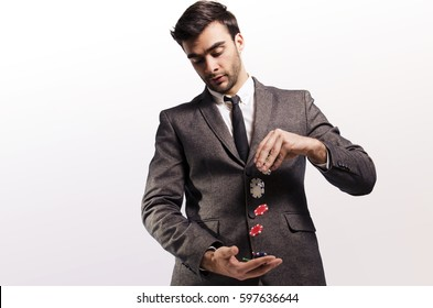 Handsome businessman in suit, throwing poker chips from one hand to the other / risky business investment concept/ risk taker