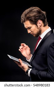 Handsome businessman in suit using digital tablet isolated on black