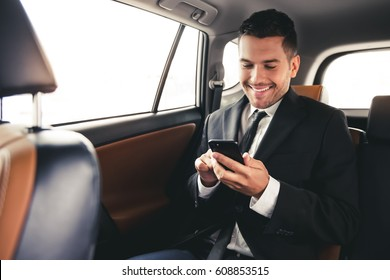 Handsome businessman in suit is using a smart phone and smiling while sitting on back seat in the car
