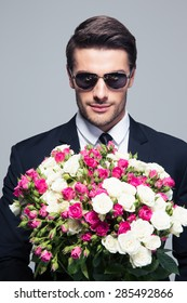 Handsome businessman in sunglasses holding flowers over gray background