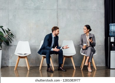 handsome businessman talking to asian businesswoman in waiting hall