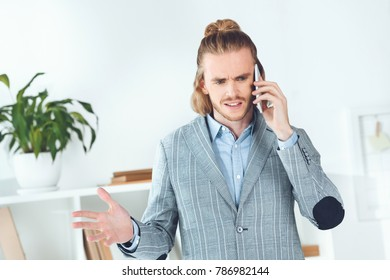 handsome businessman talking by smartphone in office