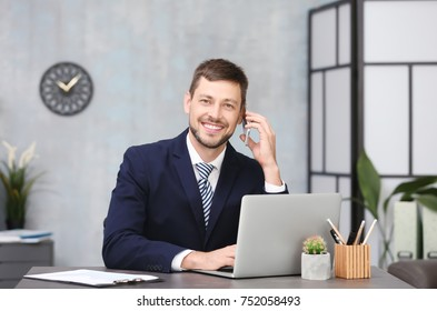Handsome businessman talking on mobile phone while working in office