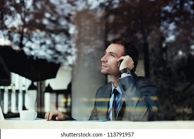 Handsome businessman talking on the phone in coffee shop.