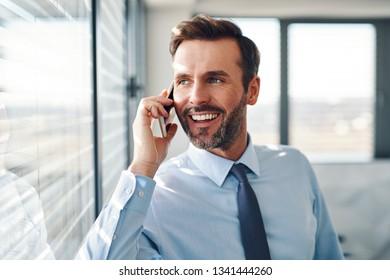 Handsome businessman talking on phone in modern office