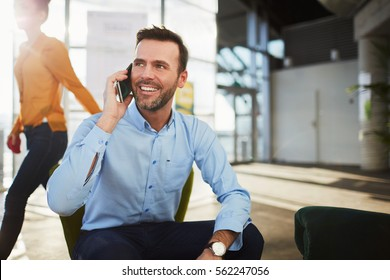 Handsome businessman talking on the phone during coffee break in a cafe