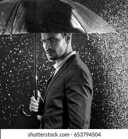 Handsome businessman under an umbrella, standing in the real rain