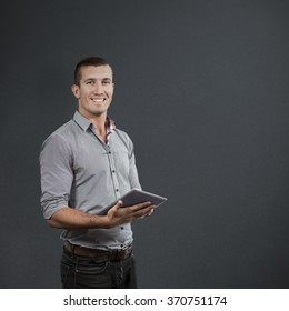 Handsome businessman using digital tablet over white background against grey background