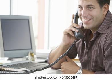 Handsome businessman using landline phone with computer at office desk