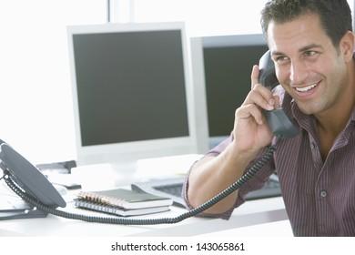 Handsome businessman using landline phone at office desk