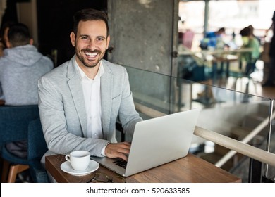 Handsome businessman using laptop at city cafe. Toothy smile.