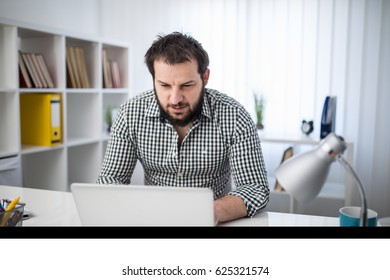 Handsome businessman using laptop in office