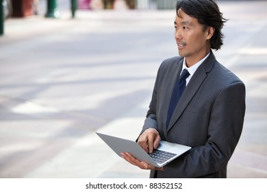 Handsome businessman using laptop outdoors