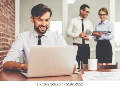 Handsome businessman is using a laptop and smiling while working in office, his colleagues are studying documents in the background