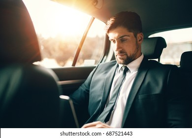 Handsome businessman using laptop while sitting on back seat of a car. Caucasian male business executive travelling by a car and working on laptop computer.