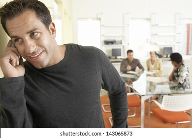 Handsome businessman using mobile phone with colleagues discussing in background