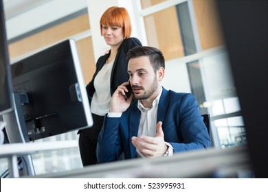 Handsome businessman using mobile phone at office.